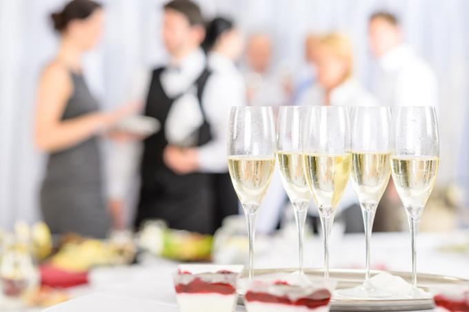 シャンパングラスが5個並ぶテーブルの奥で男女がおしゃべりをしている