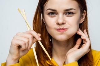 箸を持ち、ほおをふくらます女性