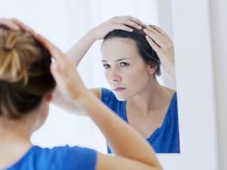 鏡で髪を見る女性