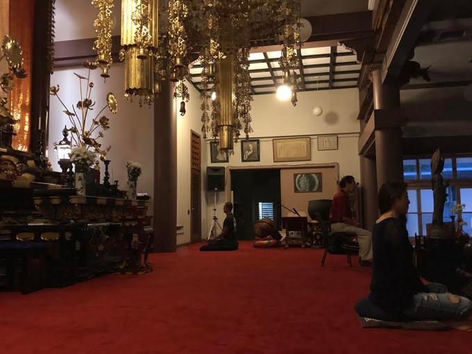 お寺で坐禅をする人々