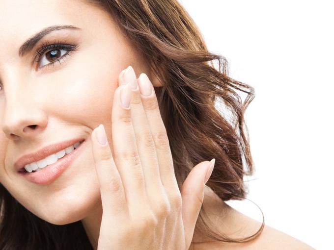 顔を触る笑顔の女性の画像
