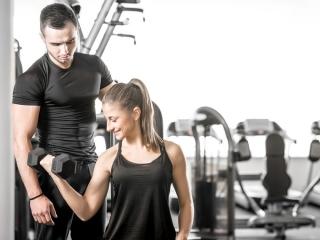 男性が女性のトレーニングをサポートしている画像
