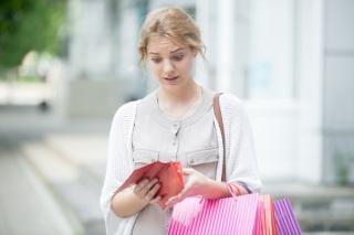 財布を開いてびっくりする女性