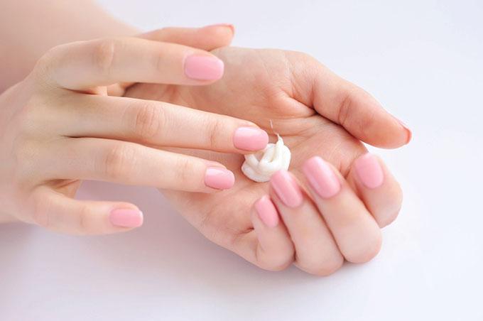 手の平にクリームを取る女性の画像