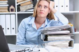 パソコンを前に、机の上で肘をついて上を見上げる女性