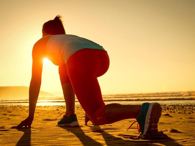 朝日のなか、トレーニングをする女性