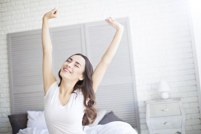 朝起きてすがすがしくのびをする女性