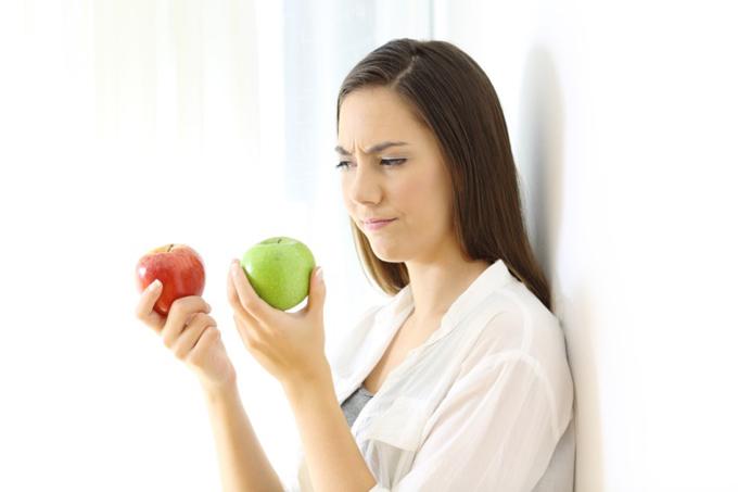 りんごを片手に思い悩む女性