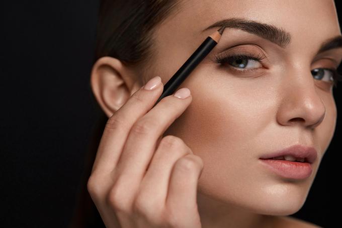 眉毛を描く女性の画像