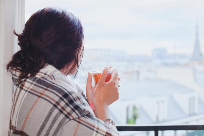肩にストールを巻き、温かい飲み物をもって窓の外を見る女性