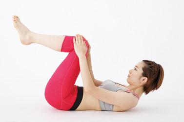 女性のモデルが仰向けでひざに手を添えている