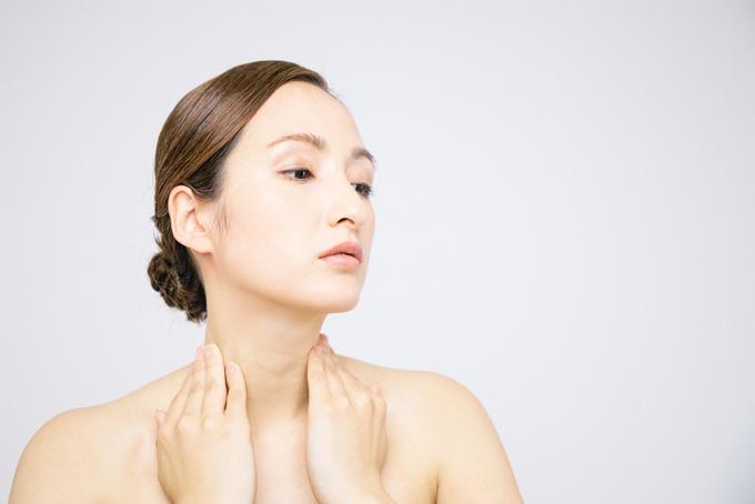 首筋を自分でマッサージする女性の画像