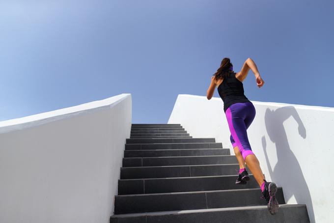 階段を駆け上がる女性の後ろ姿の画像