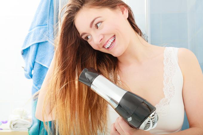 ドライヤーで髪の毛を乾かす女性
