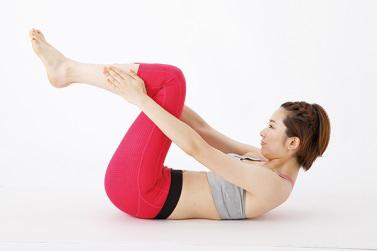 女性のモデルが仰向けでひざに手を伸ばして顔を上げている