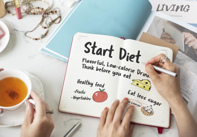 ダイエットプランをノートに書いている