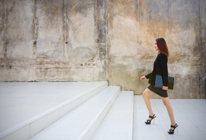 スーツで階段をのぼる女性