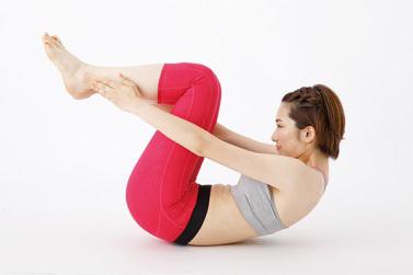 女性のモデルが仰向けで上体を大きく起こし、丸くなっている