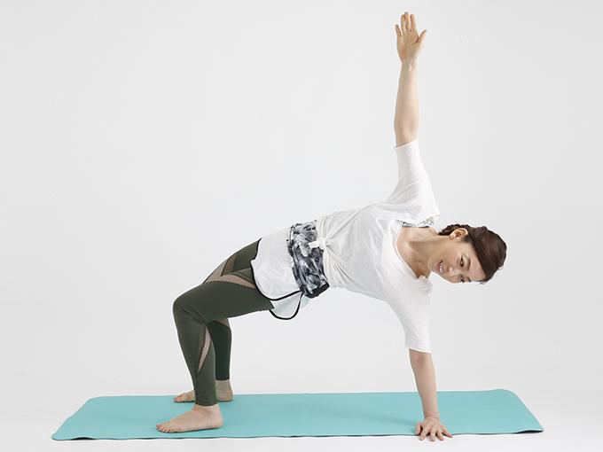 両脚と左腕で体を支え、右腕を天井へ伸ばす