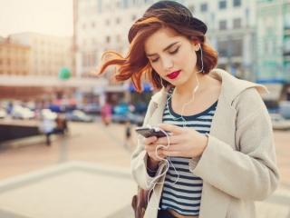 女性が街中でスマホを操作している画像