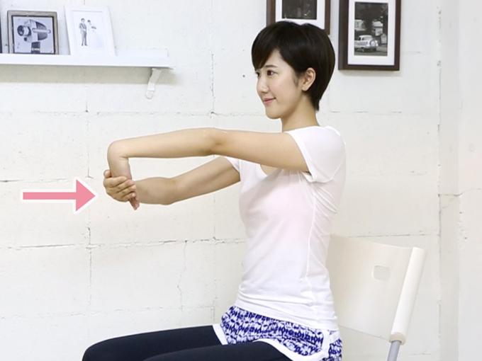 腕の外側を伸ばすストレッチの写真