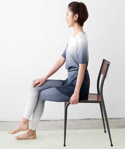 イスに腰かけ、脚を組む