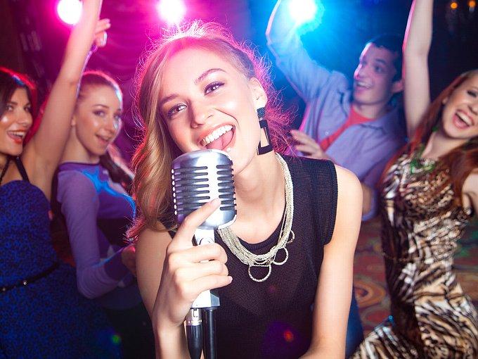 スタンドマイクを持ち歌う女性と、後ろで盛り上がる男女4人