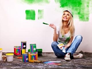女性がペンキを壁に塗っている