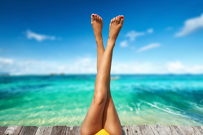 背景が海、美脚を上に上げている脚だけの写真