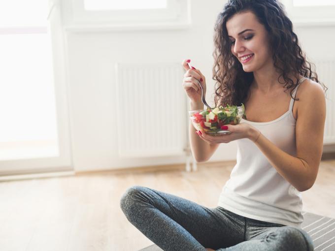 野菜サラダを食べている女性の画像