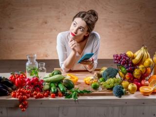 食材に囲まれた女性が首をかしげている画像
