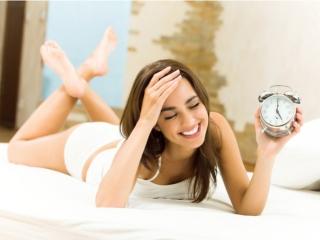 女性が目覚まし時計をもって笑っている写真