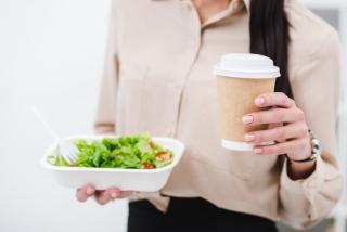 サラダとコーヒーを持っている女性