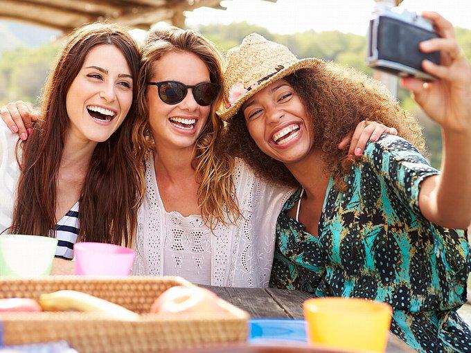カメラで写真をとる女性3人