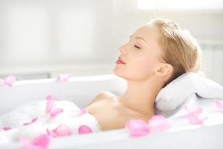 薔薇の花びらが浮いたお風呂で入浴する女性の画像