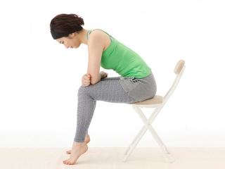 イスに座りながら自重筋トレを行う写真
