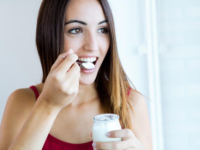 ヨーグルトを食べていきいきとした女性