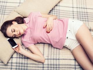 スマートフォンで音楽を聞きながら寝ている女性の画像