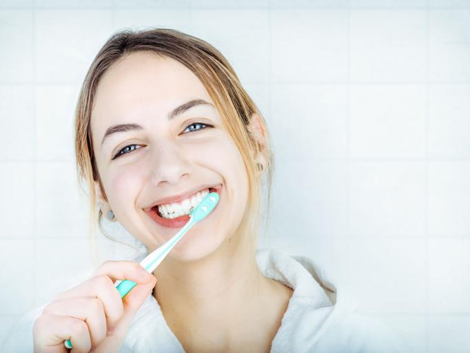白い歯ブラシで歯磨きをする女性の画像