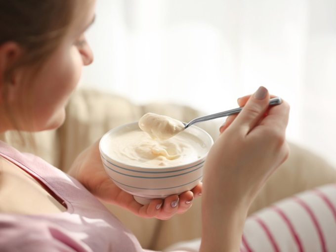 ヨーグルトをスプーンですくって食べる女性