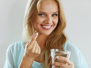 お水でサプリメントを飲もうとする女性