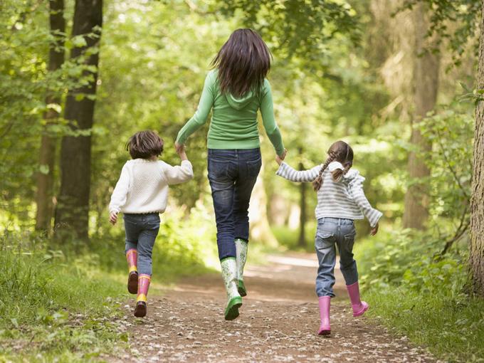 森の中でスキップする親子の画像