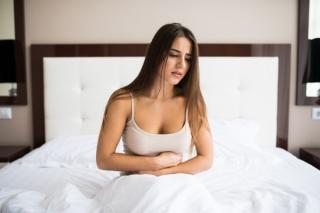 ベッドの上でお腹を押さえる女性