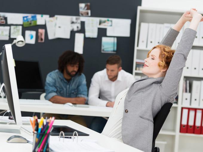パソコンの前で伸びをする女性の画像