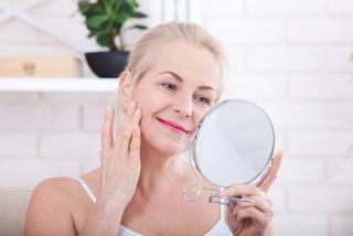 鏡を見る中年女性の画像