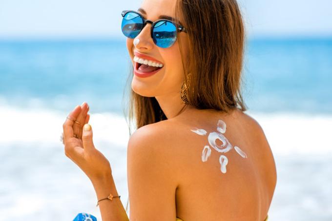 背中に日焼け止めで太陽マークを書き、こっちを向いて微笑む女性