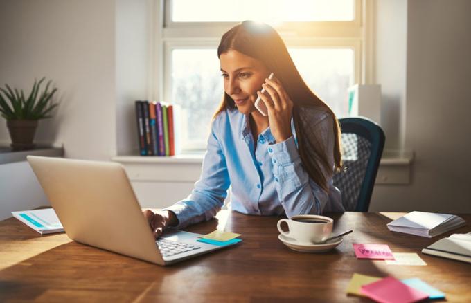 窓際のデスクで仕事をする女性