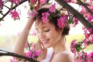 マゼンタ色の小花に囲まれた女性