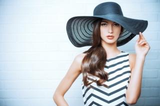 白い壁の前に立つ帽子をかぶった女性