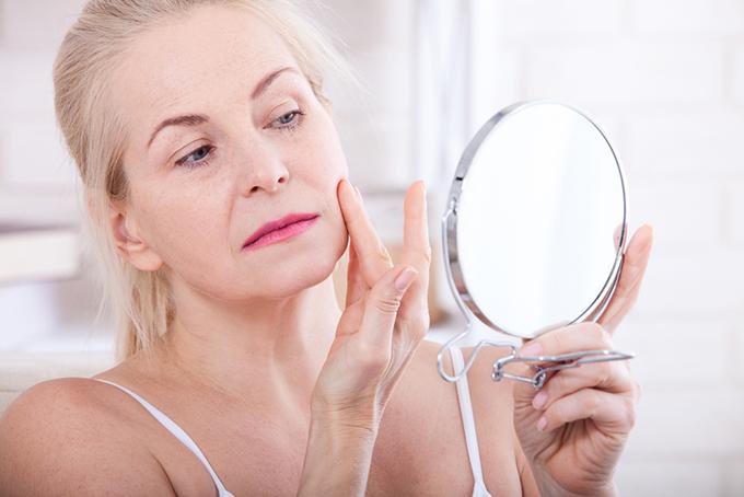 鏡を見る中年女子の画像